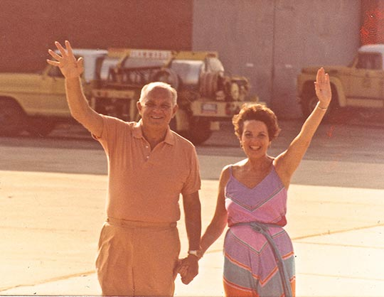 Gramie and Grandad waving to the camera in an unknown airfield