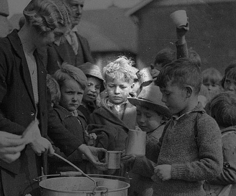 Schoolchildren line up for free issue of soup and a slice of bread / 1934