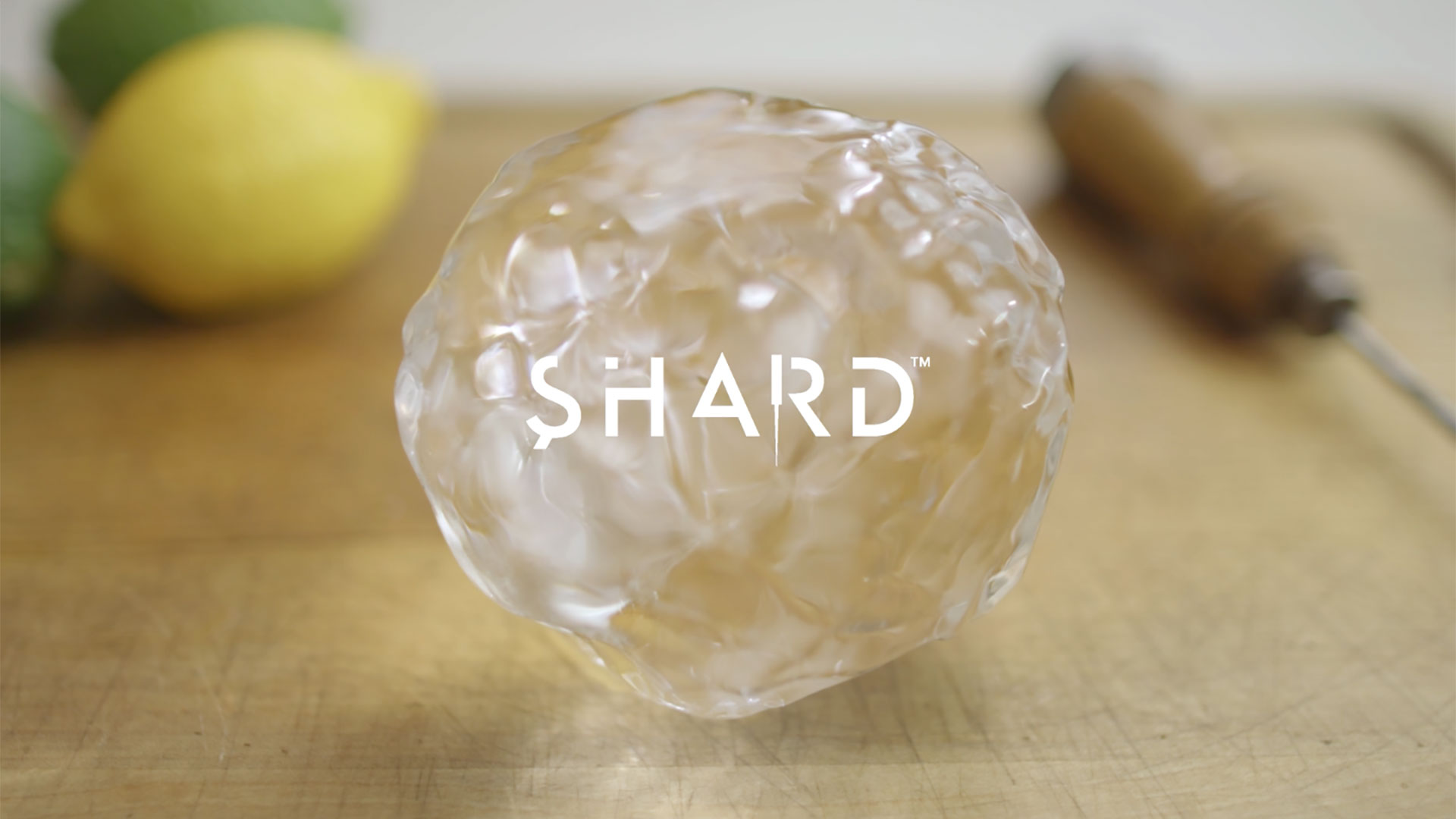 Hand-carved ice ball on a cutting board overlaid with the Shard logo, with lemon, lime, and ice pick in the background